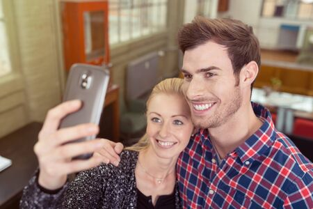 close together: Young couple posing for a selfie on their mobile phone standing with their heads close together smiling into the camera