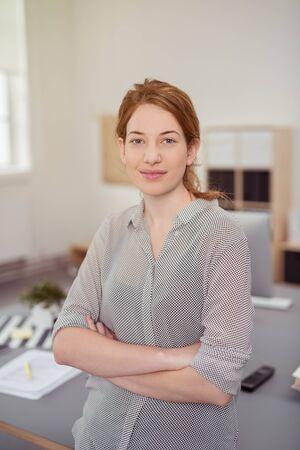 trabajo oficina: Encuadre cintura para arriba Retrato de confianza empresaria joven con el pelo rojo de pie en la oficina moderna con los brazos cruzados