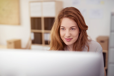 ejecutivo en oficina: Mujer joven atractiva que trabaja en una computadora de escritorio sonriendo mientras se inclina hacia delante para leer texto en la pantalla, ver el monitor