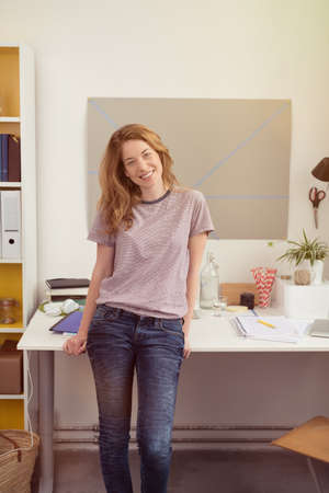 lovely businesswoman: Smiling relaxed young businesswoman in jeans working from home standing sitting on the edge of her desk looking at the camera with a lovely warm smile Stock Photo