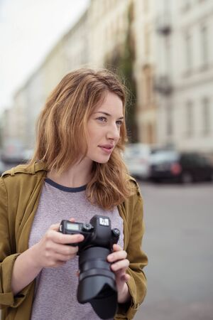 dslr camera: Young woman visualising a photograph as she stands in an urban street holding her camera and squinting into the distance