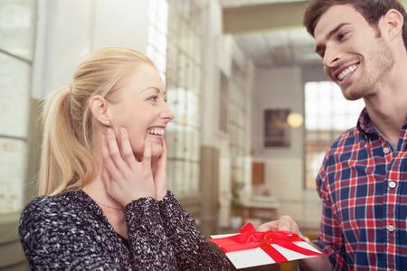 sorpresa: Marido sonriente hermoso que da a su joven y bella esposa rubia un regalo sorpresa atado en un lazo rojo decorativo Foto de archivo