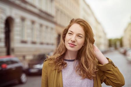 caras felices: Atractiva mujer joven de pie en una calle urbana pensamiento profundamente mirando a un lado con una expresión lejana y su mano a su cabello