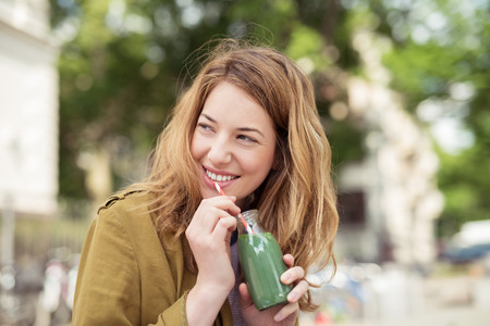 green drink: Pretty Blond Teen Girl Drinking a Bottle of Green Juice with Straw While Smiling Into Distance.