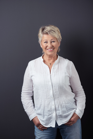 60 years: Portrait of a Cheerful Matured Woman in Casual White Shirt and Jeans, Standing Against Gray Wall Background and Smiling at the Camera. Stock Photo
