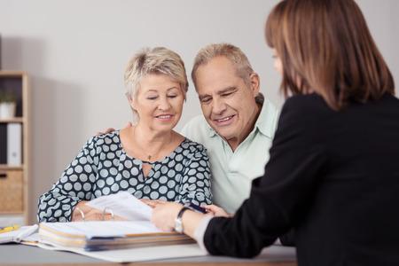 Zoete Senior paar luisteren naar een Vrouwelijke Hypotheek Agent hen uit te leggen binnen het kantoor.