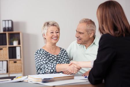 Gelukkige midden oude Vrouw naast haar man Handen schudden met een vrouwelijke business agent aan de tafel.