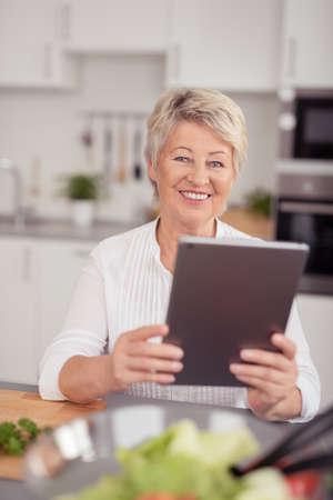cocina antigua: Cerrar una feliz mujer mayor en la cocina, que sostiene un ordenador de la tablilla mientras que prepara algo de comer