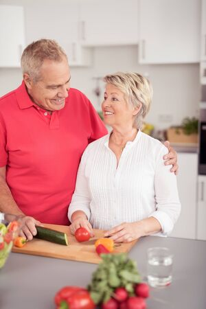 pareja saludable: Happy Middle Aged Couple Smiling Each Other While Preparing Something for Dinner at the Kitchen