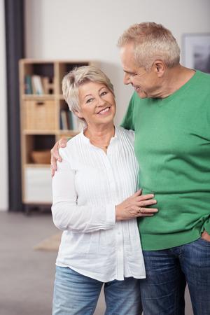 Gelukkig Midden Oud Paar in casual kleding, Standing So Sweet in het huis Terwijl Vrouw Kijkend naar de camera.