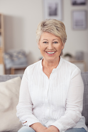 old lady: Portrait of a Cheerful Blond Middle Aged Woman Sitting at the Sofa in the Living Room, Looking at Camera with a Toothy Smile. Stock Photo