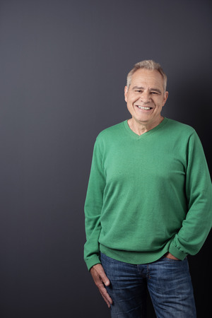 grey haired: Three-quarter length of happy senior grey haired man with hand in pocket wearing green sweatshirt and denim jeans on black background Stock Photo