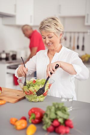 cocina antigua: Feliz Ama de casa envejecida media Preparación saludable ensalada de verduras frescas en un recipiente de vidrio en la cocina
