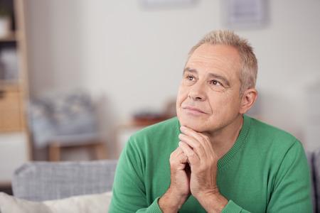 hombres maduros: Pensativo hombre de mediana edad mirando al vacío con una expresión seria y la barbilla apoyada en las manos, vista de cerca en su sala de estar