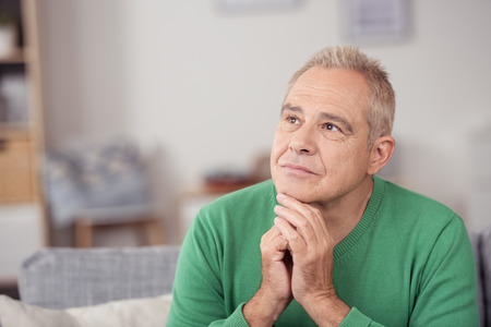 aged person: Thoughtful middle-aged man staring into space with a serious expression and his chin resting on his hands, close up view in his living room