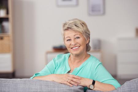 Portret van een mooie Senior blonde vrouw zitten op de bank met Wapens Leunend op de kussens, die bij Camera glimlacht