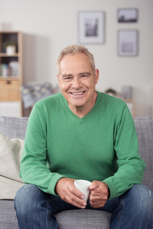 Elderly man sitting enjoying a cup of coffee on a sofa in his living room giving the camera a beaming smile