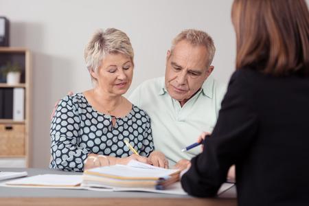 Mittlere gealterte Paare, die etwas behandeln auf dem Dokument an weibliche Agent an den Tisch.