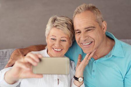 abuelos: Cierre de dulce feliz pareja de mediana edad que se sienta en el sofá, Tomando selfie fotos usando el teléfono móvil.
