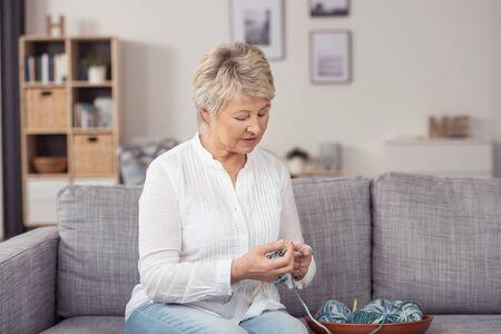 trabajo manual: Mujer de mediana edad en ropa casual, sentado en el sofá de la sala y hacer punto con hilado serio