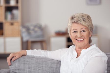 Close-up Gelukkige midden oude vrouw zitten aan de woonkamer met een arm op de bovenste rand van de Bank, en bij de Camera glimlacht. Stockfoto