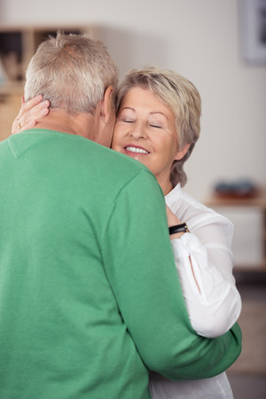old age: Close up Romantic Middle Aged Couple Embracing One Another While Dancing Sweet Music Inside the House.