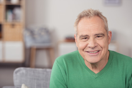 personas sentadas: Retrato de un hombre de mediana edad en camisa ocasional verde, sentado en la sala de estar mientras sonriendo a la cámara. Foto de archivo