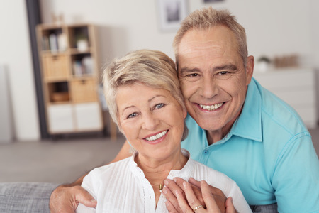 couple on couch: Portrait of a Happy Sweet Middle Aged Couple Smiling at the Camera While at the Living Area Inside the House. Stock Photo
