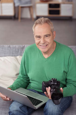 photographer: Portrait of a Smiling Senior Male Photographer with his Laptop Computer and DSLR, Smiling at the Camera Stock Photo