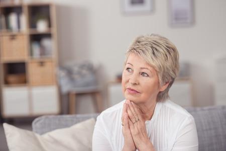 mujeres maduras: Close up pensativo Mujer rubia envejecida media, sentado en la sala de estar y que mira para arriba con las manos en la barbilla.