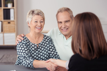 satisfied people: Happy Senior Couple Shaking Hands with Female Financial Agent at the Table While Making a Deal.