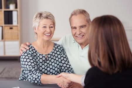 personas comunicandose: Pares mayores felices que sacuden las manos con Mujer Agente Financiero en la mesa mientras que hace una oferta.
