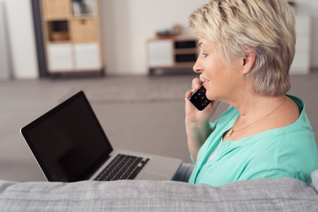 vejez feliz: Cierre de vista lateral de una mujer mayor con el ordenador portátil, hablando con alguien en el teléfono en la sala de estar. Foto de archivo