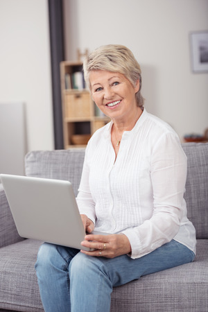 60 70: Happy Middle Aged Blond Woman Holding her Laptop Computer While Sitting on the Couch and Smiling at the Camera. Stock Photo