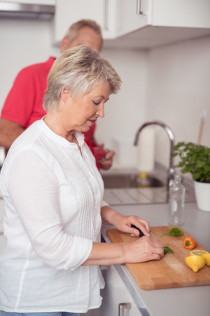 senior women: Pretty Middle Aged Housewife Slicing Fresh Ingredients for Dinner Recipe on a Wooden Cutting Board at the Kitchen.