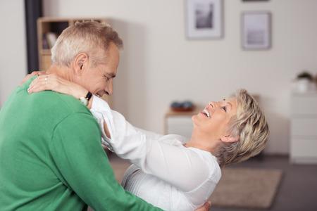 Baile envejecido medio feliz pareja en la sala de estar bien abrazados y riendo. Foto de archivo