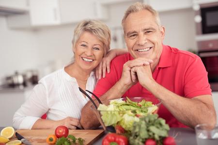 Portret van een gelukkige senior paar zitten aan de keukentafel met een kom verse salade, bij de Camera glimlacht.