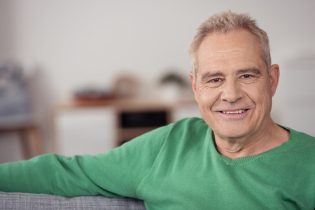 old man smiling: Close up Senior Blond Man in Green Shirt, Sitting on Sofa at Home and Smiling at the Camera Stock Photo