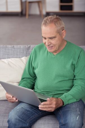 Smiling Middle Aged Man in Casual Outfit, Relaxing on the Couch at the Living Room While Using his Laptop Computer.