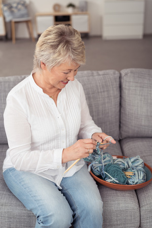 contentment: Middle-aged woman sitting on a comfortable sofa in her living room knitting a garment with a smile of contentment