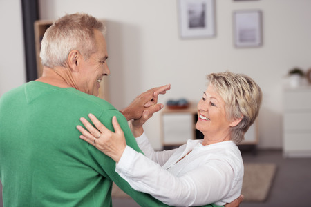vejez feliz: Baile envejecido medio que activa tan dulce Mientras sonrientes el uno al otro en la sala de estar dentro de su casa Foto de archivo