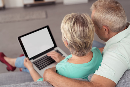 Romantic Senior Couple Browsing Internet Using a Laptop Computer While Relaxing at the Couch In the Living Room.