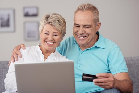 vejez feliz: Cierre de dulce feliz pareja de ancianos sentados en el sof�, usando un ordenador port�til para algunos de transacciones en l�nea.