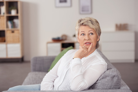 in thought: Thoughtful Middle Aged Blond Woman Sitting on the Couch at the Living Room, Looking Up Seriously with Hand on her Face.