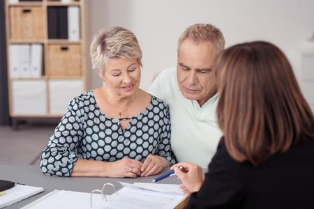 甘い中高齢者カップルを聞いて彼らに議論ビジネス女性エージェント テーブルにドキュメントってください。 写真素材