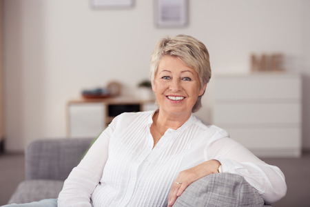 long sleeved: Close up Cheerful Senior Woman in Casual White Long Sleeved Shirt, Sitting at the Gray Couch In the Living Room and Smiling at the Camera.