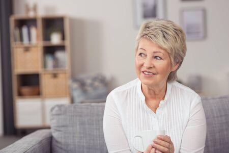 mujer pensativa: Retrato de un sonriente pensativo Madurado Mujer con una taza de café, sentado en el sofá mientras mira a Distancia Foto de archivo