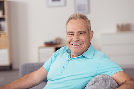 Portrait of a Senior Man in Casual Sky Blue Polo Shirt, Relaxing at the Couch and Smiling at Camera in Close up