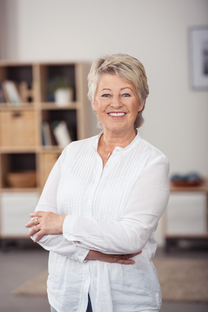 long sleeved: Portrait of a Confident Middle Aged Woman in White Long-Sleeved Shirt, Smiling at the Camera with Arms Crossing Over her Stomach.