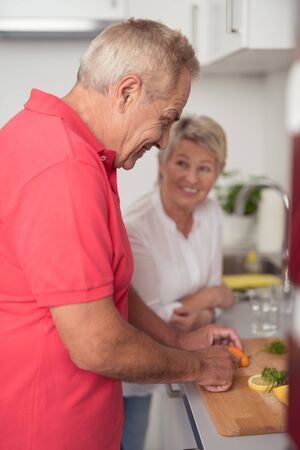 pension cuts: Happy Middle Aged Couple Preparing Something Homemade Fresh Food for Dinner at the Kitchen Stock Photo